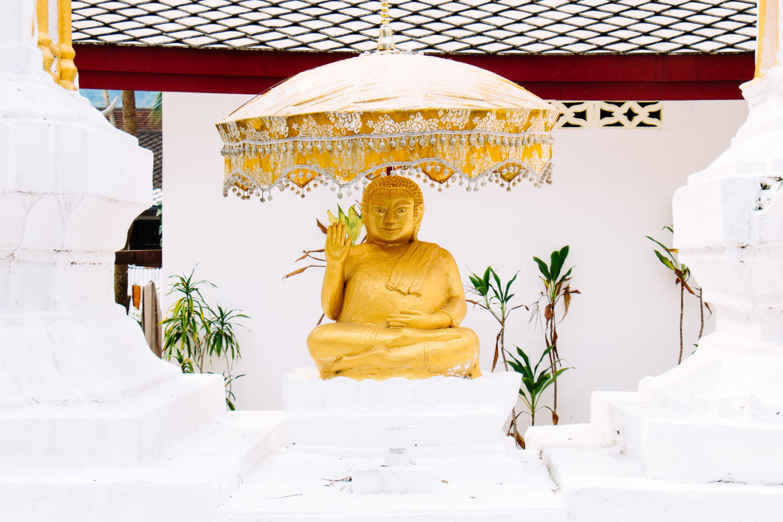 Golden buddha under umbrella in temple in Luang Prabang, Lao