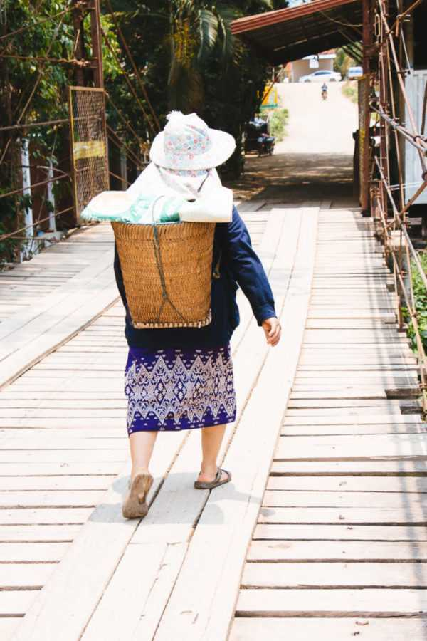 Old woman crossing bridge in Vang Vieng