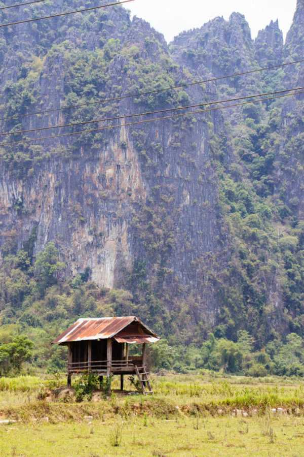 Wooden hut in front of karst landscape