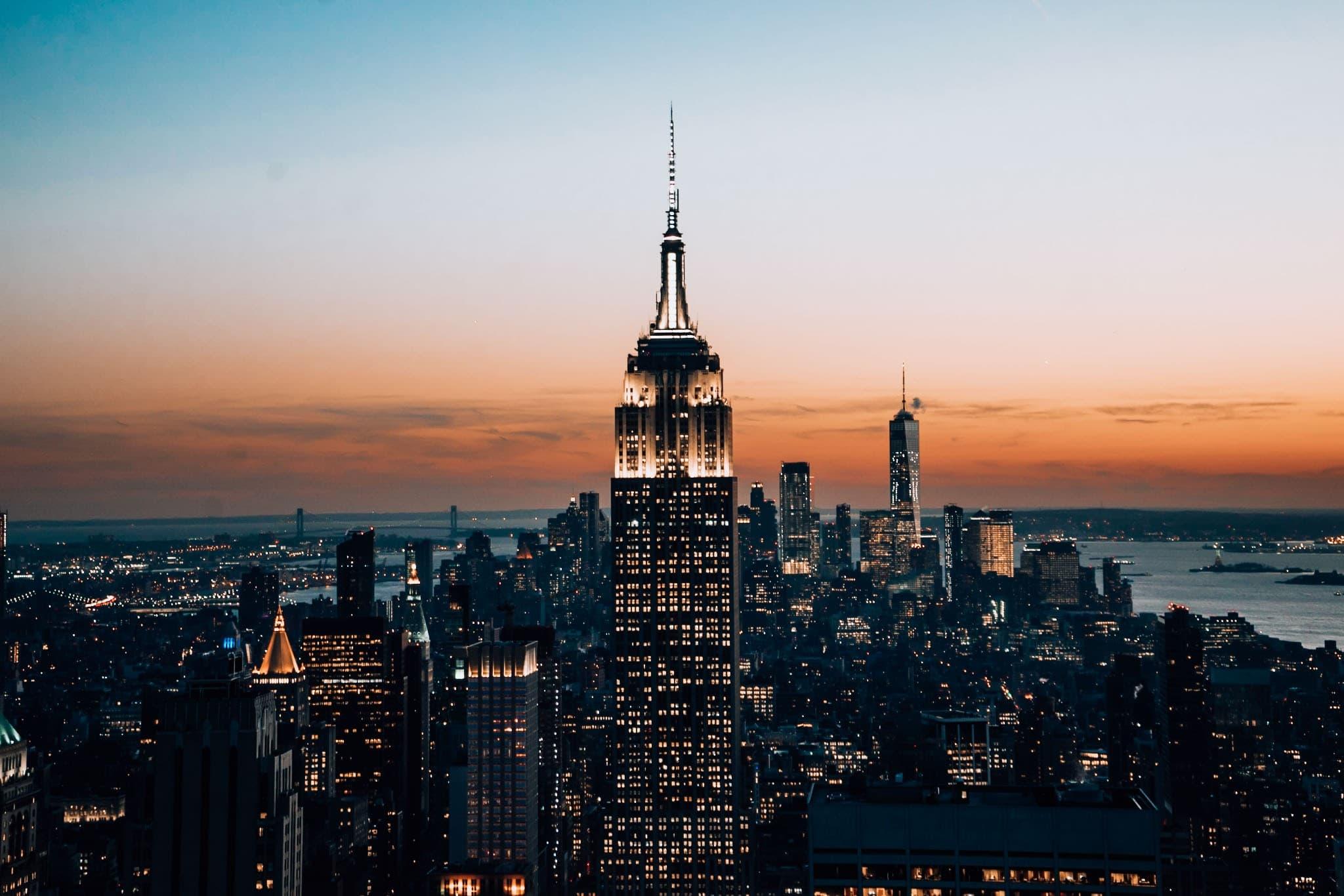 Empire State Building bei Nacht vor orangenem Sonnenuntergang