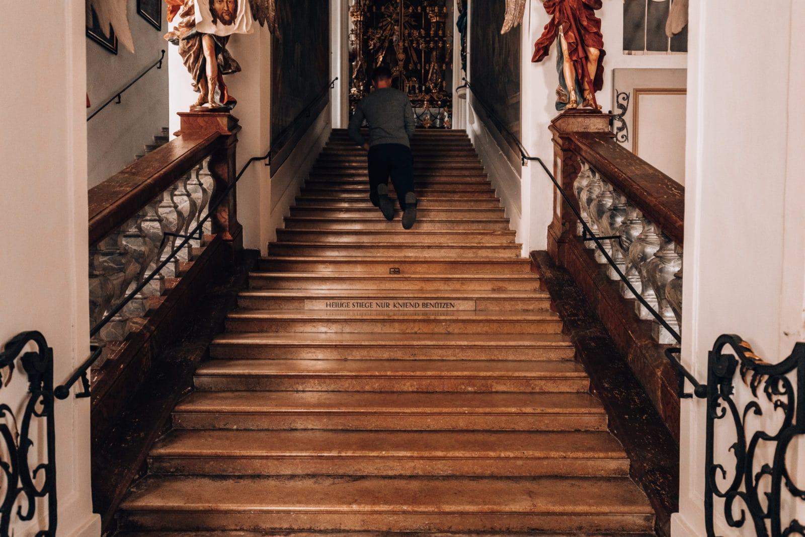 Auf Knien auf der Scala Santa in der Kajetanerkirche in Salzburg