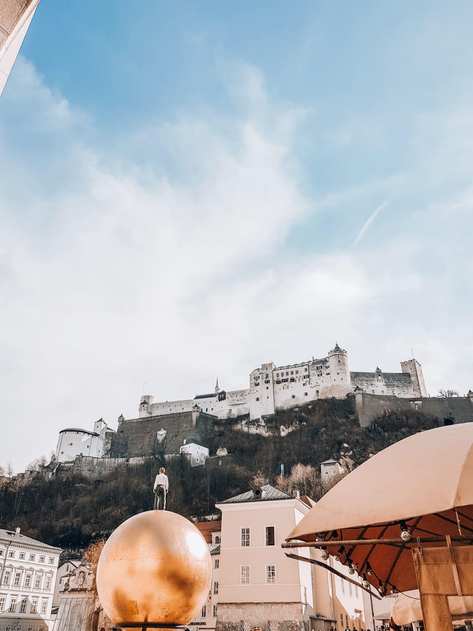 Skulptur Mann auf goldener Kugel in Salzburg vor Festung Hohensalzburg