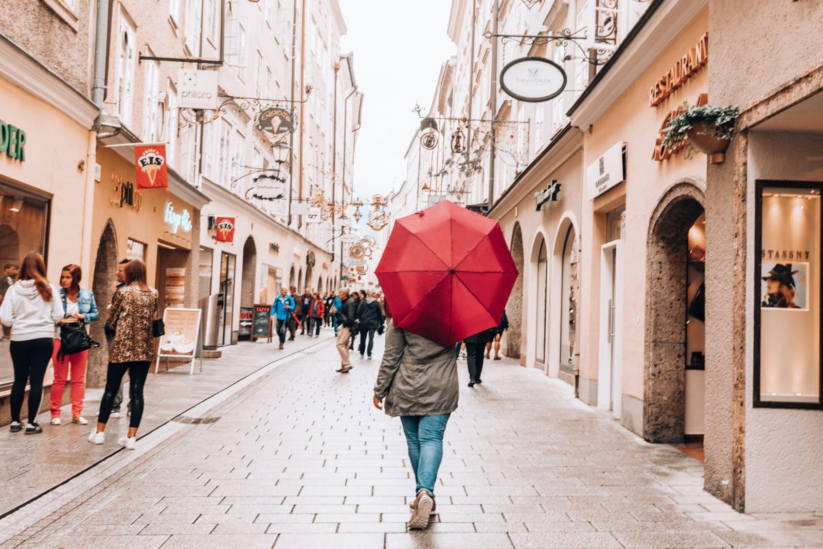 Frau mit Schirm in Salzburger Altstadt bei Schnürlregen, Regen in Salzburg