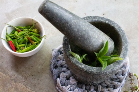 Mortar with herbs for curry paste and bowl with chilli peppers